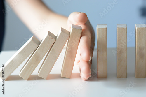 Fotografia  Stopping the domino effect concept with a business solution and intervention