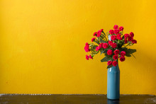 Red Flowers In Vase On Yellow Background