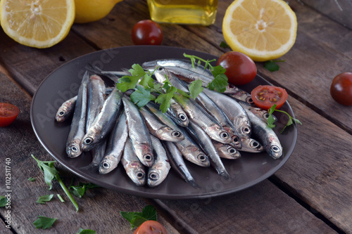 Photo  fresh anchovies, placed on a wooden table