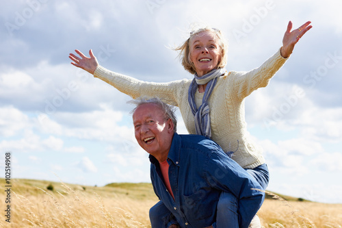 Fotografie, Obraz  Senior Man Carrying Senior Woman On Walk In Countryside