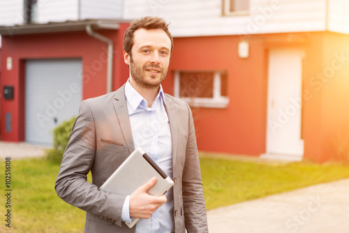 Photo  Portrait of a young real estate agent in front of a house