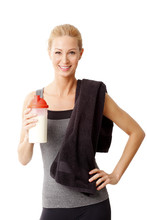 Portrait Of A Woman With A Towel Around Her Neck Holding A Protein Shaker And Standing Against White Background.