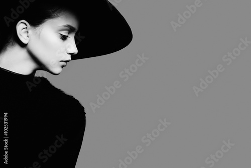 Plakat Portrait of beautiful girl in hat in profile, posing in studio, black and white