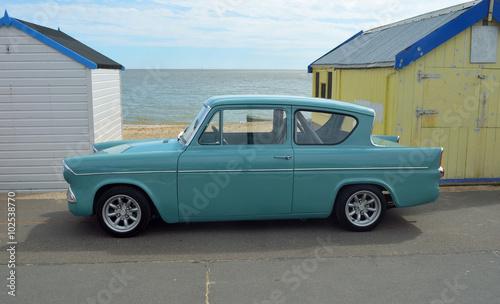 Photo  Classic blue Ford Anglia by beach huts on Felixstowe promenade.
