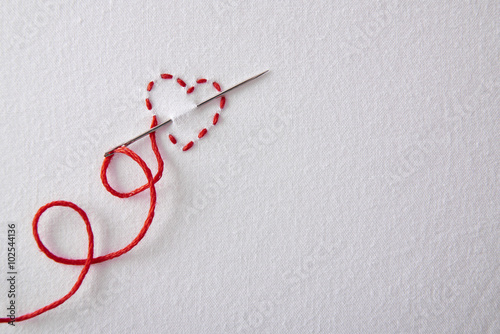 Fotografiet  Embroidered red heart on a white cloth top view