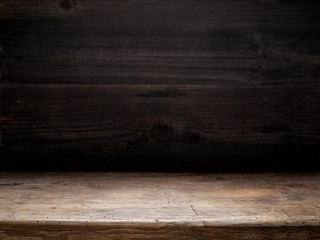 Fototapeta wooden table and dark wooden wall