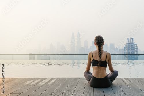Spoed Foto op Canvas School de yoga Relaxed young yoga woman in yoga pose near pool.