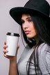 Close up Woman in black hat with cup of hot drink - isolated on grey background. Series of poses.