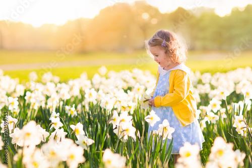 Deurstickers Narcis Little girl in daffodil field