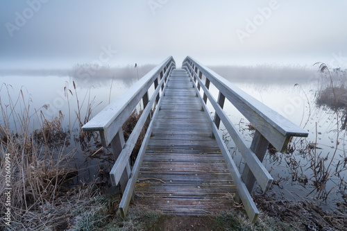 obraz lub plakat wooden bridge via river in winter