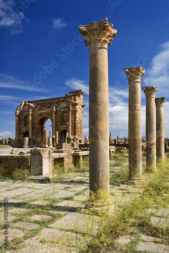 Poster Algérie Algeria. Timgad (ancient Thamugadi or Thamugas). View on Trajan's Arch via the Sertius market with stone stalls surrounded by Corinthian columns