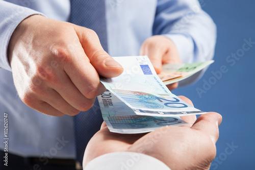 Fototapeta Businessman's  hands exchanging euro on blue background obraz
