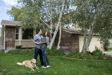 Couple And Dog In Front Of New Home Staring At Each Other With Sold Sign