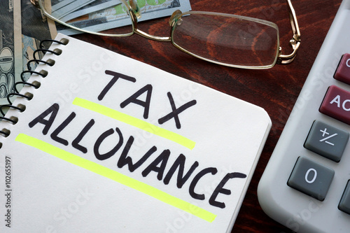 Notebook with tax allowances sign on a table. Business concept. Canvas Print