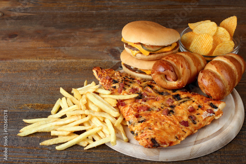 a large piece of delicious pizza and a hamburger with fries on a wooden chopping Board on brown wooden table © Studio KIVI