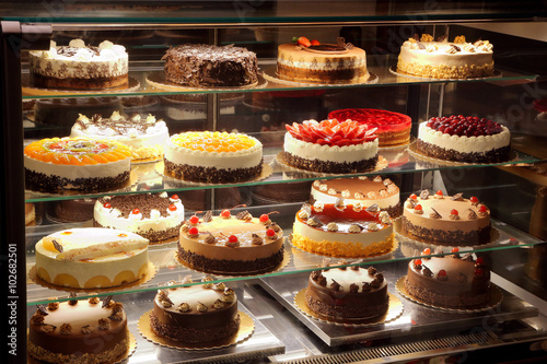 Different types of cakes in pastry shop glass display - 102682501