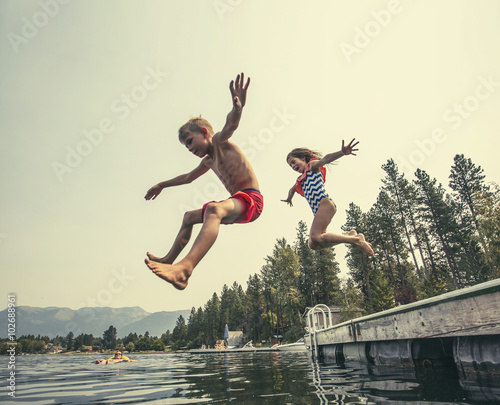 Kids jumping off the dock into a beautiful mountain lake Canvas Print
