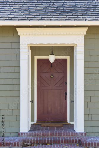 Narrow Front Door With White Trim And Green Facade