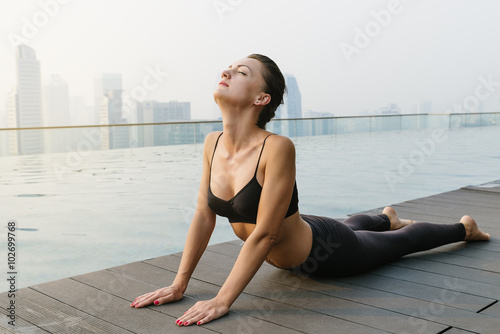Plagát  Relaxed young yoga woman in yoga pose near pool.