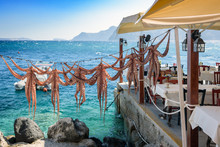 Drying Octopus Arms At Greek Tavern On Santorini Island, Traditional Greek Seafood Prepared On A Grill