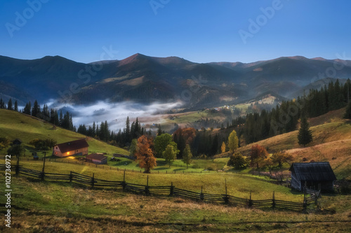 In de dag Zuid-Amerika land Carpathian Mountains. Moonlit Night in the mountains, the village on the hill in the fog