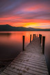 Vibrant orange/red long exposure sunset over Derwentwater in the English Lake District. The tourist-popular Ashness jetty can be seen in the foreground.