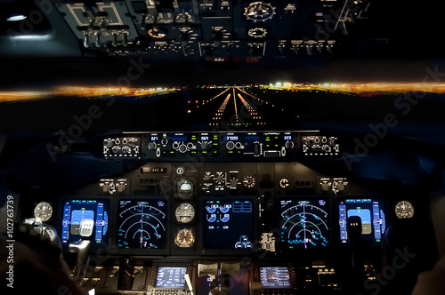 Final approach at night - landing plane flight deck view Fotobehang
