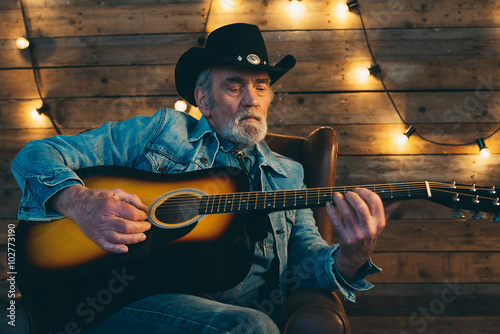 Obraz Guitar playing senior country and western musician with beard si - fototapety do salonu