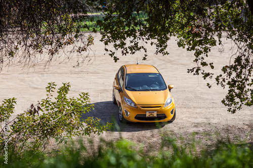 фотография  Beautiful Yellow Ford Fiesta Parked in a Dirty Road Frames With
