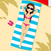 Beautiful Brunette Woman Wearing Pink Bikini Lying On The Beach On A White And Blue Striped Towel
