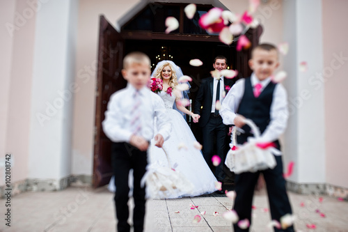 Fotografie, Obraz  Wedding couple out from church registration, children strew peta