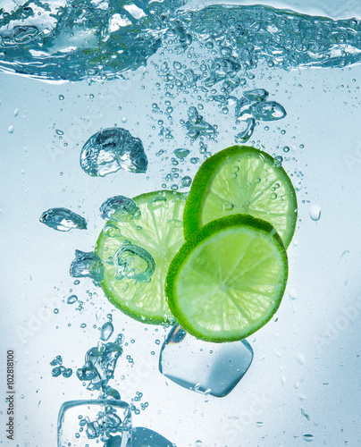 Staande foto Vruchten Limes with water splash and ice cubes