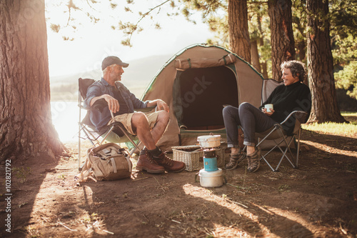 Poster Camping Couple relaxing on chairs by tent at campsite