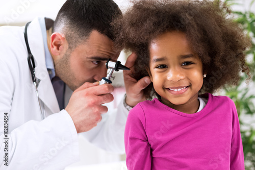 Fotografia  Smiling little african girl with ear specialist