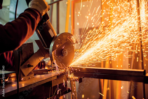 Slika na platnu Electric grinder / A man working with electric grinder tool  on steel structure