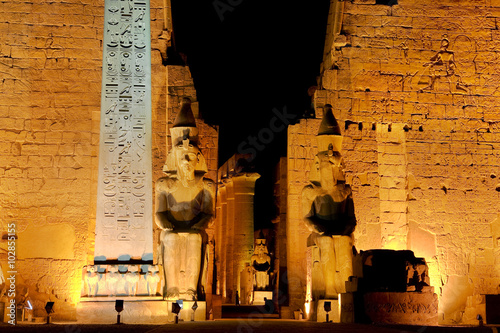 Tuinposter Egypte Egypt. Illuminated Luxor Temple. The red granite obelisk and two seated statues of Ramesses II in front of the first pylon