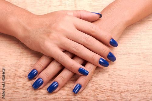 Photographie  Femme mains avec manucure bleu et vernis à ongles