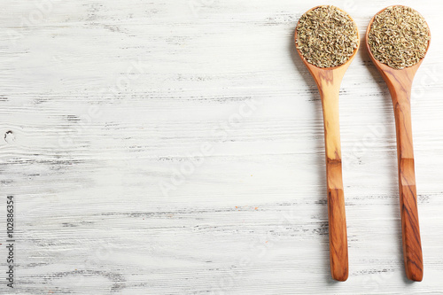 Foto auf Leinwand Gewürze 2 Two wooden spoons with cumin on the table, close-up
