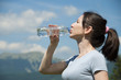 girl drinks water from a bottle on the background the mountains