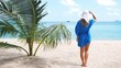 Beach vacation. Hot beautiful woman in sunhat and bikini standing with her arms raised to her head enjoying looking view of beach ocean on hot summer day. Photo from Thailand.