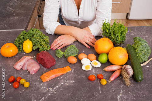 Photo Woman in kitchen with variety of vegetables and raw food