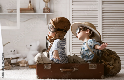 Fotografia  Boys in images traveler and pilot play in his room