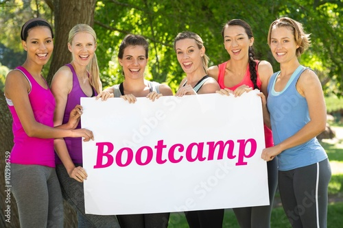 Fotografie, Obraz  Bootcamp against fitness group holding poster in park