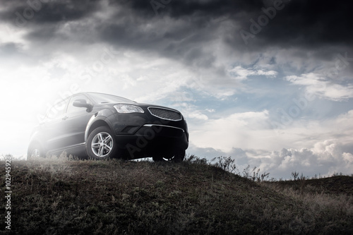 Spoed Foto op Canvas Grijze traf. Black car stay on hill in dramatic clouds at daytime