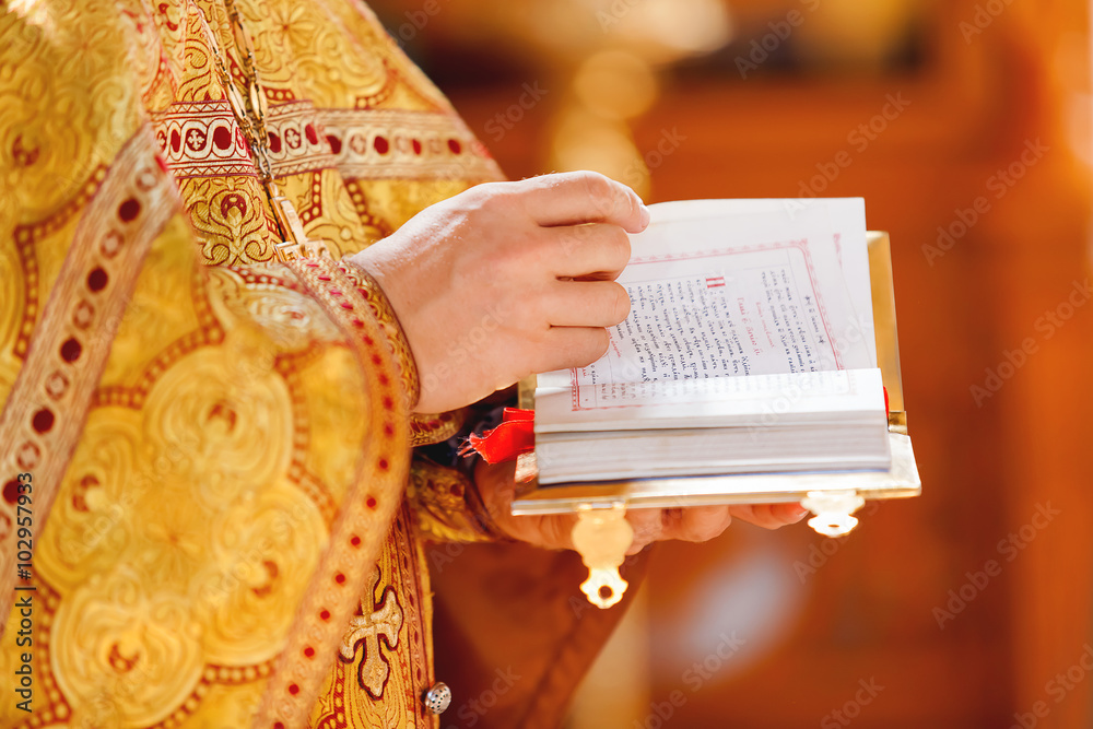 Fototapety, obrazy: Prayer book in the hands of the priest. Ceremony in the Orthodox Christian Church. Russia.