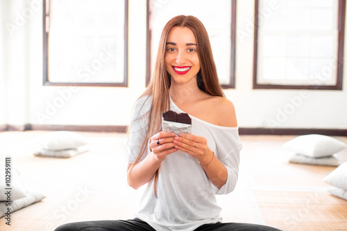 Woman eating black chocolate in the gym Plakát
