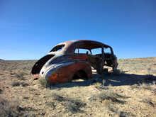Abandoned Shell Of Antique Car With Bullet Holes - Landscape Color Photo