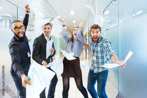Group of joyful excited business people having fun in office