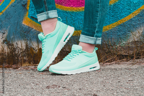Fotografia  Peppermint sneakers on girl legs on the graffiti background