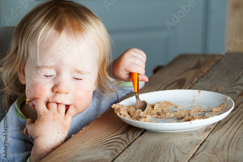obraz dibond baby eating porridge at the table